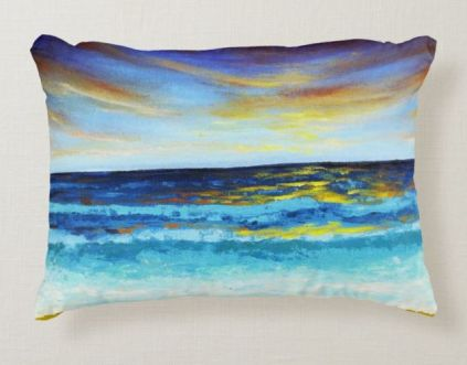 Pillow decorated with artwork of a seashore at sunset.