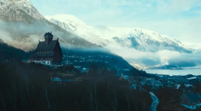 A large building with the appearance of a Norse stave church overlooks a small town in the valley.